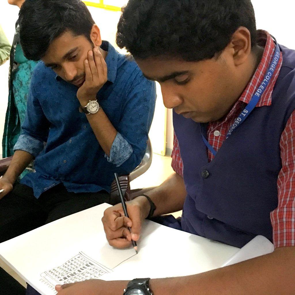 Pranav Varma drawing while Vilas Nayak watches